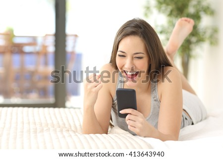 Excited winner checking online the phone for a prize lying on the bed at home with a window in the background - stock photo