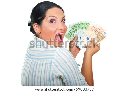 Excited winner woman holding a lot of money and looking over shoulder with a surprised  face isolated on white background - stock photo