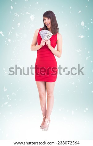 Excited woman holding american dollars against blue vignette - stock photo