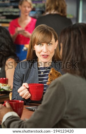 Excited woman holding cookie with friend in cafe