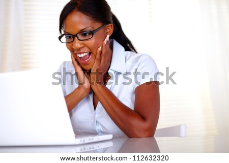 Excited woman looking to laptop screen with black glasses at workplace - copyspace - stock photo