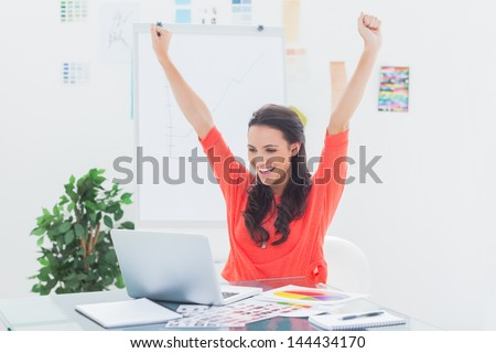 Excited woman raising her arms while working on her laptop in her office - stock photo