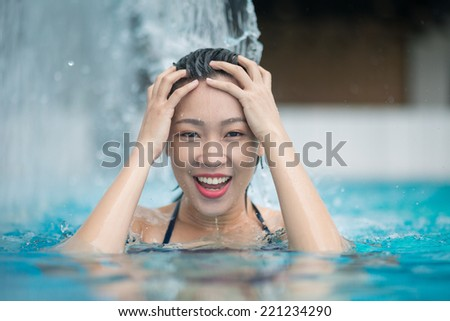 Excited woman refreshing in the pool under the small waterfall - stock photo