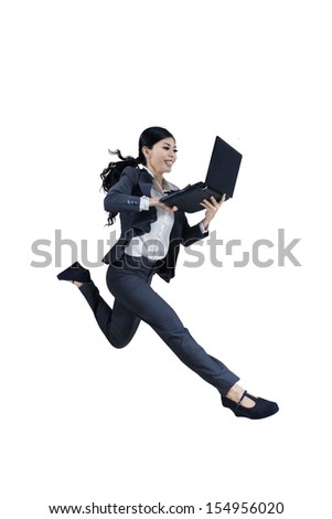 Excited woman running and holding a laptop on white background - stock photo
