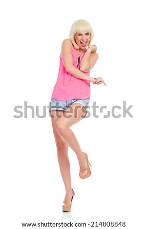Excited woman standing on one leg and pointing. Shouting blonde young woman in high heels and pink top standing on one leg and pointing. Full length studio shot isolated on white. - stock photo