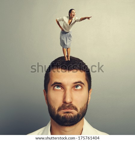 excited woman standing on the head and pointing - stock photo