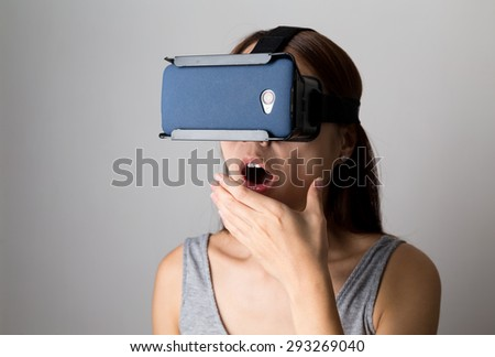 Excited woman watching though the VR device - stock photo