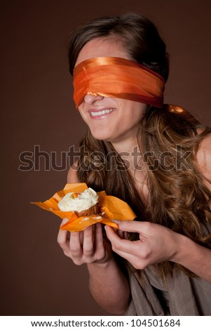 Excited woman wearing blindfold and holding cake - stock photo