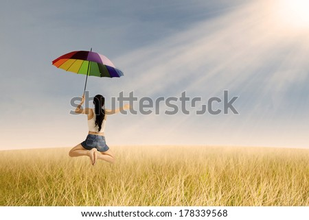 Excited woman with colorful umbrella jumping  in rice field and sunset - stock photo