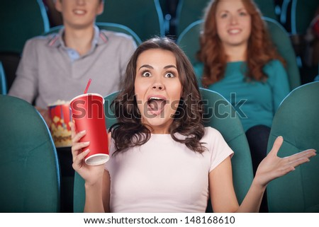 Excited women at the cinema. Beautiful young women drinking soda and gesturing while watching movie at the cinema