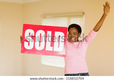 excited young african american woman with sold sign indoors - stock photo