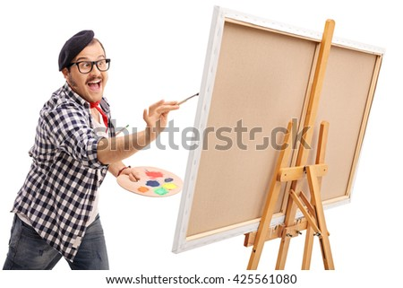 Excited young artist painting on a canvas with a paintbrush isolated on white background - stock photo