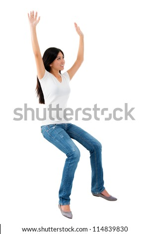 Excited young Asian girl raise her hands up, sitting on invisible chair over white background - stock photo