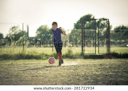 Excited young boy playing soccer - stock photo