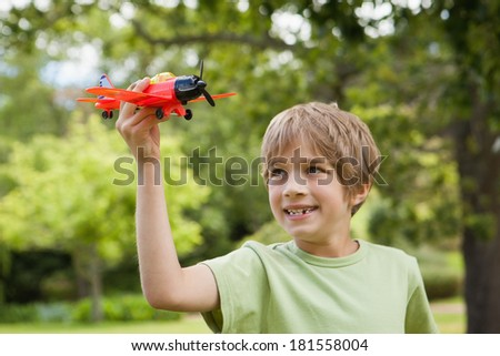 Excited young boy playing with a toy plane at the park - stock photo