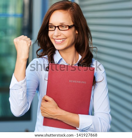 Excited young business woman with her clenched fist - stock photo