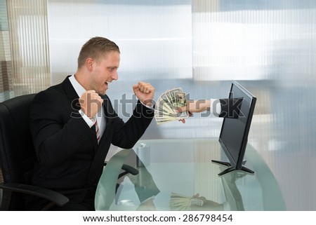 Excited Young Businessman Looking At Money Coming Out From Computer Flat Screen - stock photo