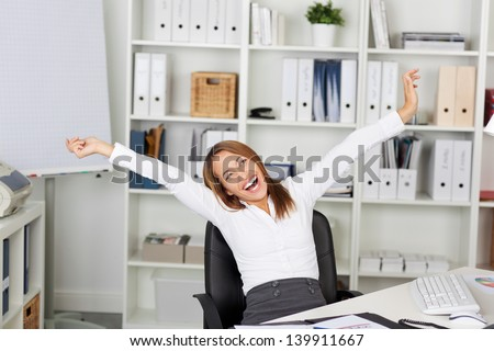Excited young businesswoman with arms raised sitting on chair at office desk