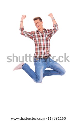 excited young casual man jumping and cheering while looking into the camera, isolated on white