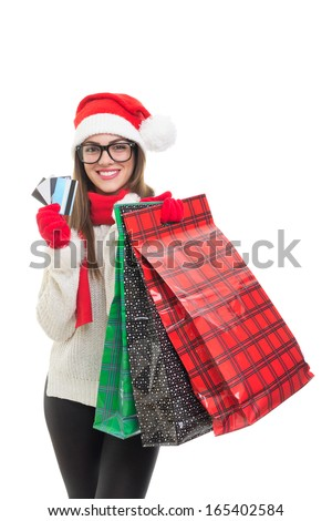 Excited young Caucasian woman at Christmas shopping. Model wearing black nerd eyeglasses and Santa Claus beanie hat smiling looking at camera holding shopping bags and credit cards.  - stock photo