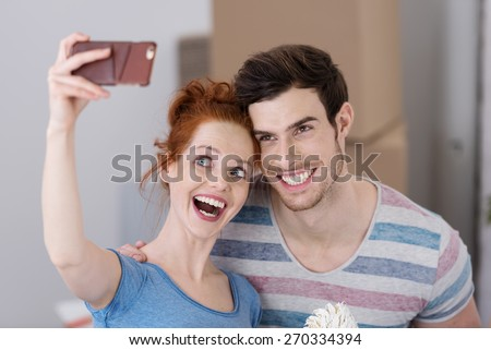 Excited young couple in a new home posing for a selfie on their mobile phone with big cheesy playful grins - stock photo