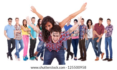 excited young couple playing in front of a large group of fashion casual people - stock photo