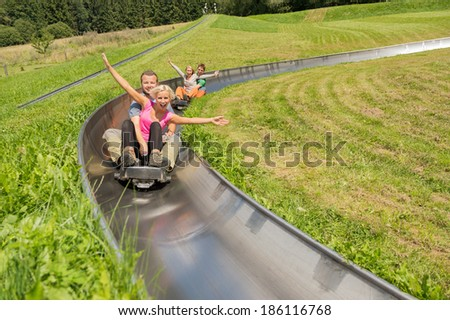 Excited young couples enjoying alpine coaster luge during summer - stock photo