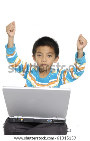 Excited young Cute asian Child working on Computer with arms up in excitement - stock photo
