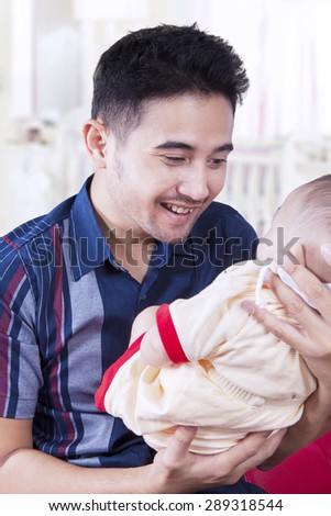 Excited young dad holding his three months baby in the bedroom and smiling on the baby - stock photo