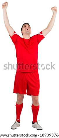 Excited young football player cheering on white background