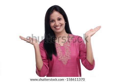 Excited young Indian girl against white background - stock photo