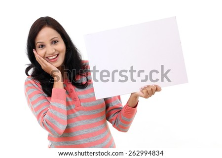 Excited young Indian woman holding billboard against white - stock photo