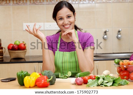 Excited young Indian woman in kitchen