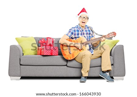 Excited young male with christmas hat sitting on a modern sofa and playing an acoustic guitar isolated on white background - stock photo
