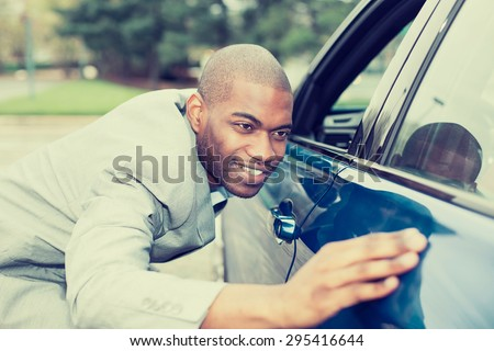 Excited young man and his new car  - stock photo