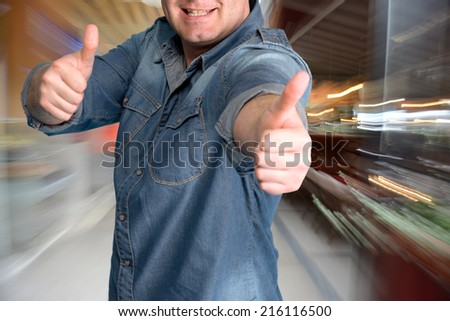 Excited young man gesturing thumbs up at shopping mall