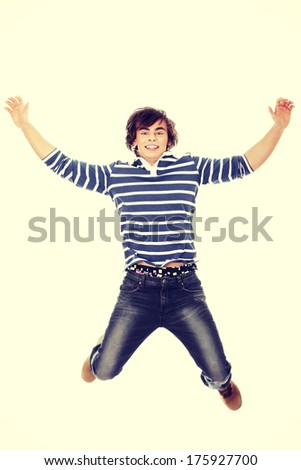 Excited young man jumping in air  - stock photo