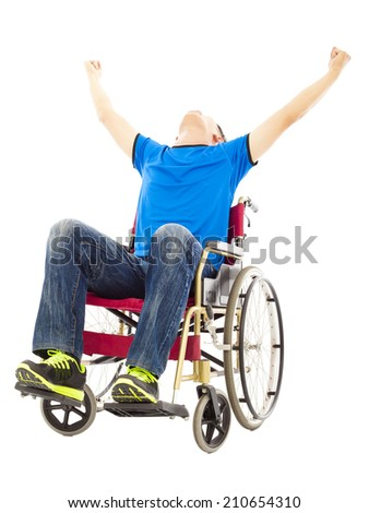 excited young man sitting on a wheelchair and raising hands - stock photo