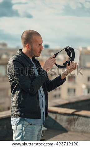 Excited young man wearing a pair of VR glasses above the city with the blue sky background amazed by augmented reality
