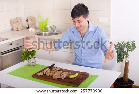 Excited young man with spread arms looking in slices of wholemeal bread and chili pepper - stock photo