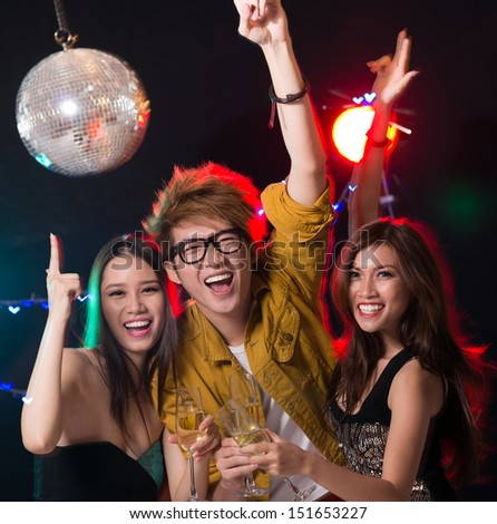 Excited young people dancing in the nightclub together