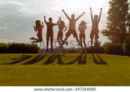 Excited young people jumping on the green meadow - stock photo