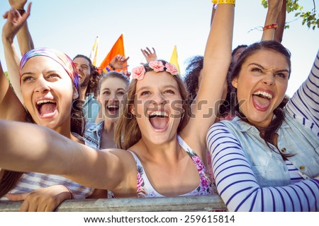 Excited young people singing along at a music festival - stock photo