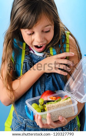 Excited young school girl holding and looking into healthy lunchbox filled with fresh fruit and sandwich on blue background - stock photo