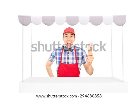 Excited young vendor with a red cap and apron holding an ice cream cone behind an ice cream stand isolated on white background - stock photo