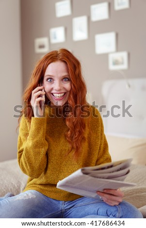 Excited young woman answering a newspaper advertisement on her mobile phone as she sits relaxing on her bed beaming at the camera - stock photo