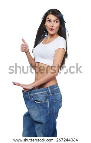 Excited young woman delighted with her dieting results, isolated on white. Happy woman with oversized jeand showing her slim waist and gesturing thumb up, looking away - stock photo
