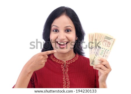 Excited young woman holding five hundred rupee notes against white