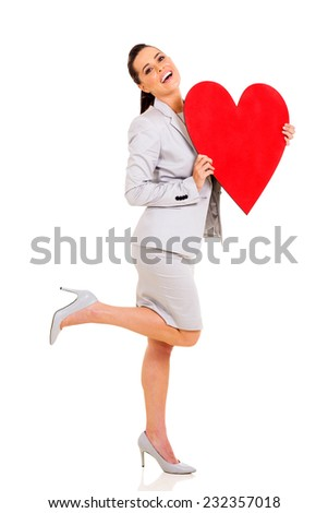 excited young woman holding heart shape over white background - stock photo