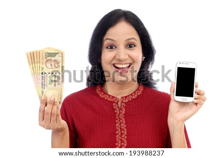 Excited young woman holding Indian currency and mobile phone - Mobile banking